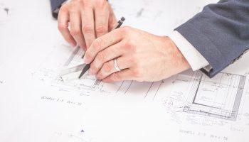 Dłonie meskie nanoszące poprawki na probejkt budowlany